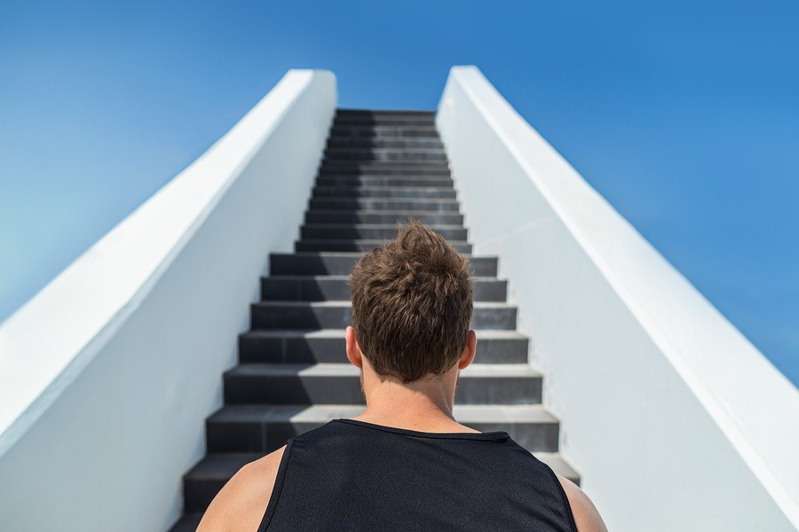 Fitness man looking ahead at stairs climbing challenge. Runner going up running staircase for cardio
